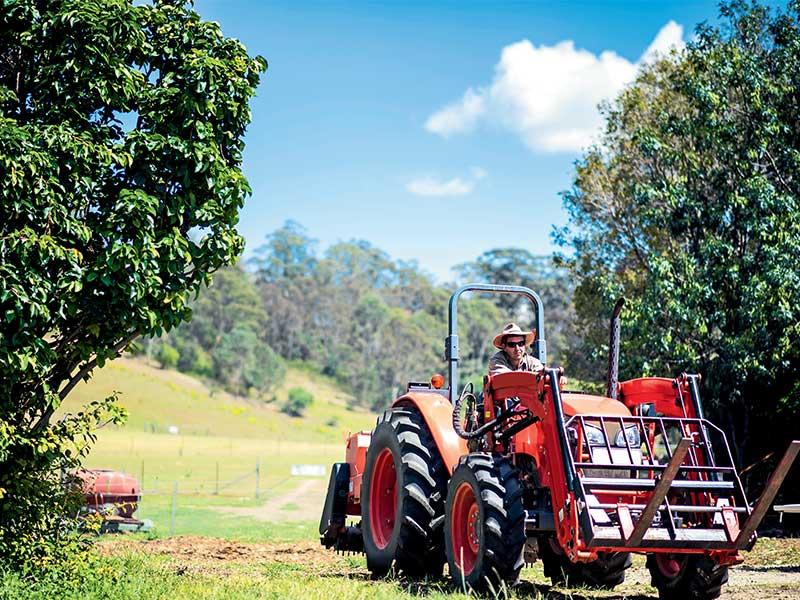 Farmer driving his small acreage tractor