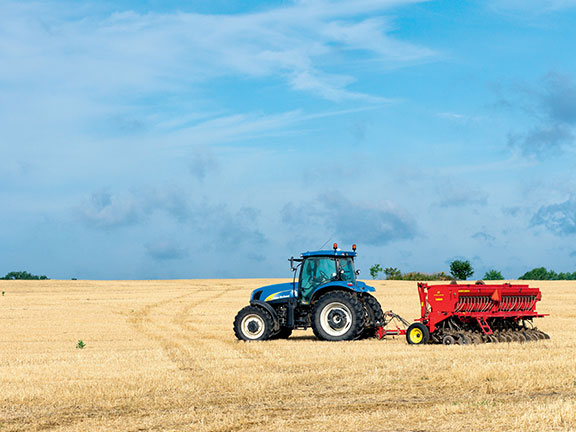 A New Holland Tractor in a field with attachment behind