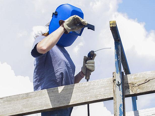 Female farm worker repairs a cattle yard with an arc welder